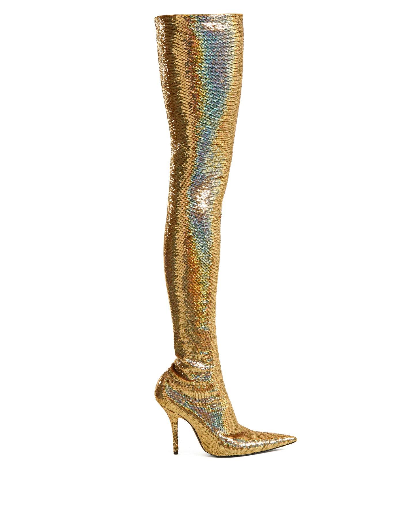 Michelle Obama indossa stivali olografici per presentare il suo libro.