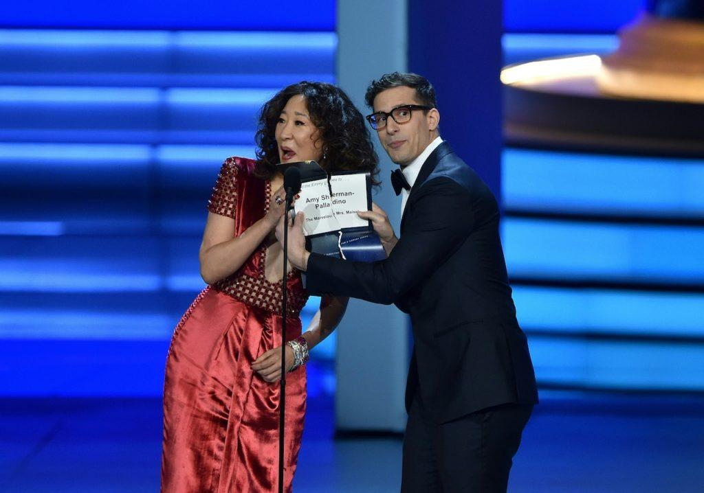 Sandra Oh e Andy Samberg sul palco del Microsoft Theater di Los Angeles mentre consegnano un Emmy Award a Amy Sherman-Paladino