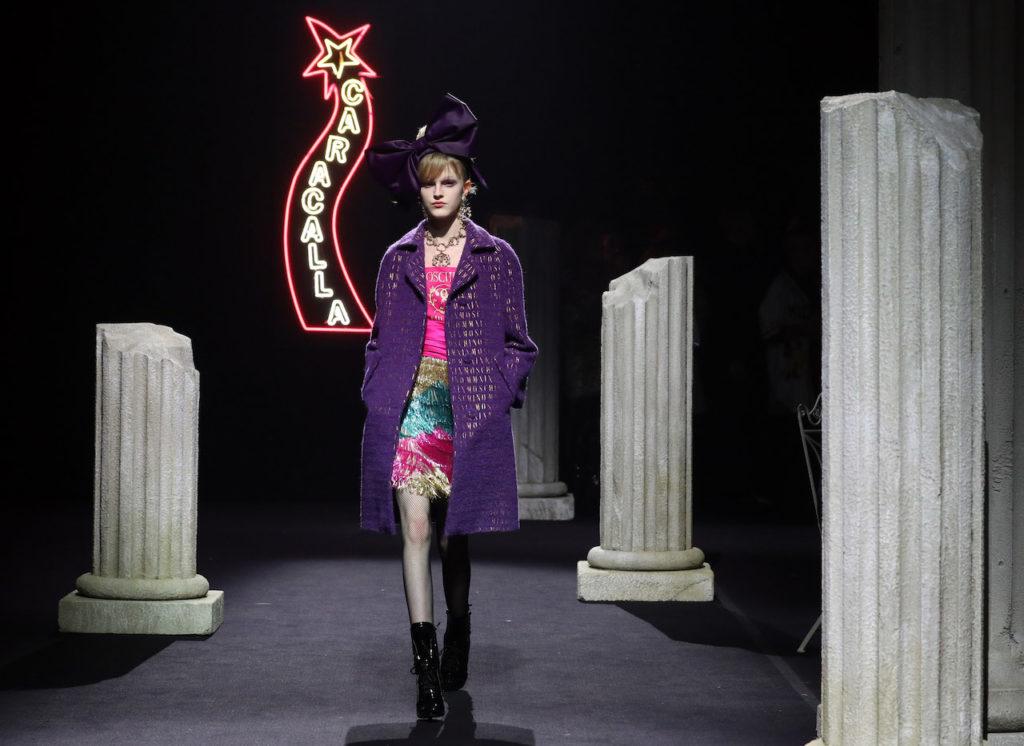 Una modella in cappotto viola sfila per Moschino